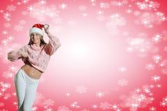 圣诞老人帽子跳舞的美丽的少妇 免版税库存图片
