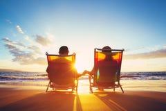 退休假期概念,观看日落的成熟小轿车 免版税库存图片