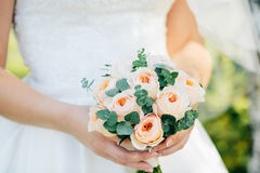 拿着与英国兰开斯特家族族徽的新娘婚礼花束 免版税库存图片