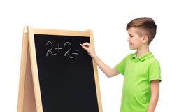 解决在学校黑板的愉快的男孩算术 免版税库存图片