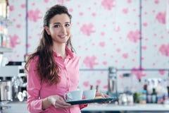 在酒吧的年轻微笑的女服务员服务咖啡 图库摄影