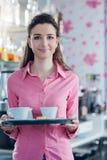 在酒吧的年轻微笑的女服务员服务咖啡 库存照片