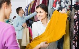 Σύμβουλος που προσφέρει τα ενδύματα φθινοπώρου πελατών στο κατάστημα Στοκ εικόνα με δικαίωμα ελεύθερης χρήσης