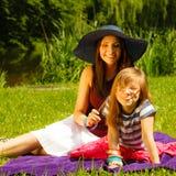 母亲和女儿小女孩有野餐在公园 免版税图库摄影