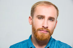 看照相机的严肃的体贴的有胡子的年轻人 免版税库存图片