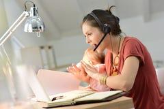 抱着她的婴孩和研究膝上型计算机的繁忙的母亲 免版税库存照片