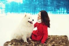 与白色萨莫耶特人狗的愉快的少妇所有者在雪在冬天 免版税图库摄影