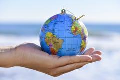 有世界地球的年轻人作为圣诞节球在他的手上 免版税图库摄影
