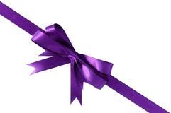 在白色背景隔绝的紫色礼物丝带弓角落对角线 库存照片