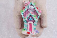 糖果土地圣诞节 在白色的女性手编织了拿着在白色的舒适手套五颜六色的糖果房子圣诞树装饰 免版税库存照片