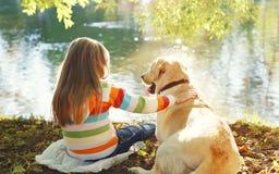 两个朋友,有坐在夏天的拉布拉多猎犬狗的孩子 免版税库存照片
