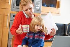在家应付紧张天的繁忙的母亲 免版税库存照片