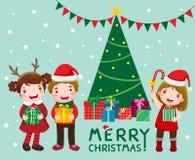 与礼物盒的愉快的逗人喜爱的孩子临近圣诞树 库存照片