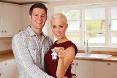 Συγκινημένα νέα κλειδιά εκμετάλλευσης ζεύγους για το νέο σπίτι Στοκ φωτογραφία με δικαίωμα ελεύθερης χρήσης