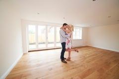 激动的年轻夫妇在空的屋子他们第一家庭里 免版税库存图片