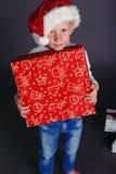 圣诞老人帽子和牛仔裤的微笑与圣诞节礼物的小男孩圣诞节照片  免版税库存图片