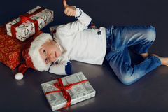 圣诞老人帽子和牛仔裤的微笑与圣诞节礼物的小男孩圣诞节照片,当前 库存图片