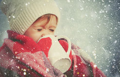有杯子的愉快的儿童女孩热的饮料在冷的冬天户外 库存图片