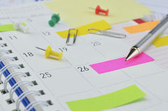 Μολύβι με τις κολλώδεις σημειώσεις και καρφίτσα στη σελίδα επιχειρησιακών ημερολογίων Στοκ Εικόνα