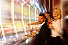 Τέσσερις νέοι που παίζουν τα μηχανήματα τυχερών παιχνιδιών με κέρματα στη χαρτοπαικτική λέσχη Στοκ φωτογραφία με δικαίωμα ελεύθερης χρήσης