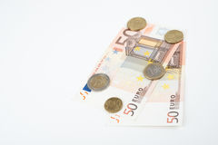 五十欧洲笔记扇动了与各种各样的欧洲硬币的前面 图库摄影