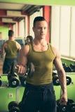 年轻运动人在健身-健身房锻炼解决 库存图片