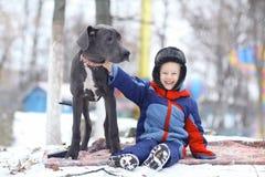 Мальчик с большой черной собакой Стоковые Изображения