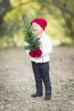 Κοριτσάκι στα κόκκινα γάντια και το μικρό χριστουγεννιάτικο δέντρο εκμετάλλευσης ΚΑΠ Στοκ εικόνα με δικαίωμα ελεύθερης χρήσης