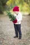 Κοριτσάκι στα κόκκινα γάντια και το μικρό χριστουγεννιάτικο δέντρο εκμετάλλευσης ΚΑΠ Στοκ εικόνες με δικαίωμα ελεύθερης χρήσης