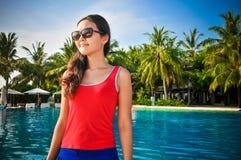 站立近的游泳池热带海滩的年轻亚裔看的妇女画象在马尔代夫 免版税库存图片