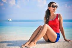 坐在游泳池附近的年轻亚裔看的妇女画象在热带海滩在马尔代夫 库存照片