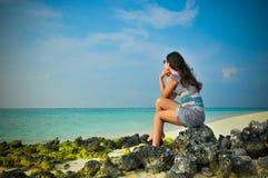 认为在热带海滩的年轻亚裔看的妇女画象在马尔代夫 免版税库存照片
