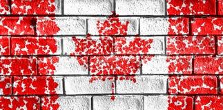 加拿大的旗子从在难看的东西砖墙上的枫叶绘了 免版税库存图片