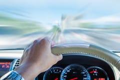 拿着方向盘的司机的手,驾驶最快速度行动 免版税库存照片