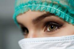 戴着防毒面具和绿色外科医生帽子的女性医生面孔 免版税图库摄影