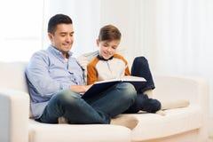 愉快的父亲和儿子阅读书在家 图库摄影
