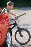 儿童骑马自行车从后面停放的汽车 库存图片