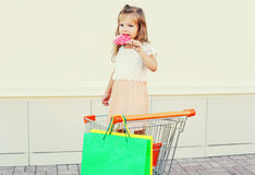 有甜焦糖棒棒糖的愉快的小女孩孩子和在台车推车的购物袋 免版税库存照片