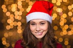 嬉戏的可爱的少妇在圣诞老人帽子 免版税库存照片