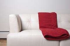 有红色毯子的白革沙发 免版税库存图片