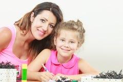 女儿帮助的家庭作业妈妈 免版税库存照片