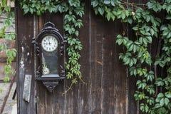 Παλαιό σπασμένο ρολόι στο φυσικό πράσινο πλαίσιο φύλλων στον ξύλινο φράκτη Στοκ Εικόνες