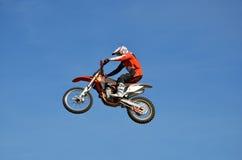 摩托车越野赛,摩托车驾驶员飞行在小山在雪外面 库存照片