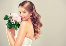 婚礼礼服的女孩新娘与典雅的发型 免版税库存照片