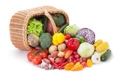在被翻转的篮子旁边的新鲜蔬菜 图库摄影