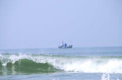 海波浪和渔夫的小船 库存图片