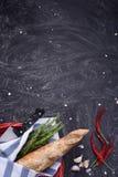 在红色篮子、迷迭香、大蒜和辣椒的新鲜的被烘烤的面包在黑暗的背景 顶视图,大方的本体空间 免版税库存图片
