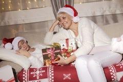 在圣诞节的妈妈和女儿充分的幸福,享用礼物 免版税库存照片