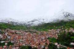 在村庄的雪山 免版税库存照片