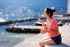 女孩在海滩的打击泡影 免版税库存图片